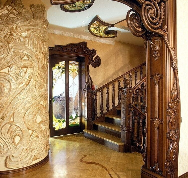 Стиль арт-нуво в интерьере. Узорчатые деревянные дверные проёмы. Отделка стен, пол, всё в узора стиля, включая лестницу